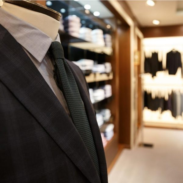 close-up-shot-of-man-suit-jacket-on-hanger-P559HWL